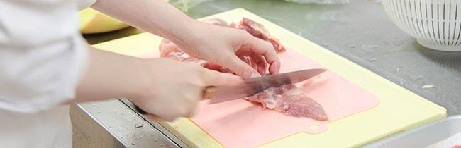 入居者の食事を作る様子、鶏肉を切っているところ